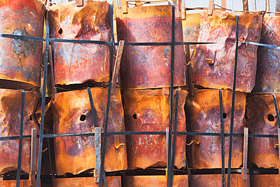 Stacked rusting barrels in a row - p924m805830f by Ditto