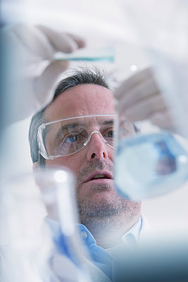 Scientist pouring liquid into measuring beaker - p924m930176f by REB Images