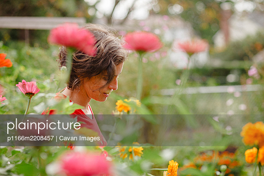 A woman stands half-hidden in beautiful patch of wildflowers in summer - p1166m2208457 by Cavan Images