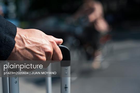 Mann mit Koffer auf einer Straße - p1423m2020604 von JUAN MOYANO