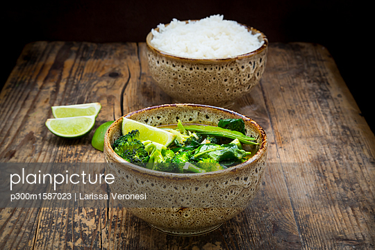 Green thai curry with broccoli, pak choi, snow peas, baby spinach, lime and bowl of rice in the background - p300m1587023 von Larissa Veronesi