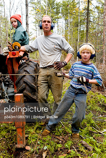 A man works with his sons clearing a forest to become organic rotational grazing fields. - p343m1089791 by Bridget Besaw