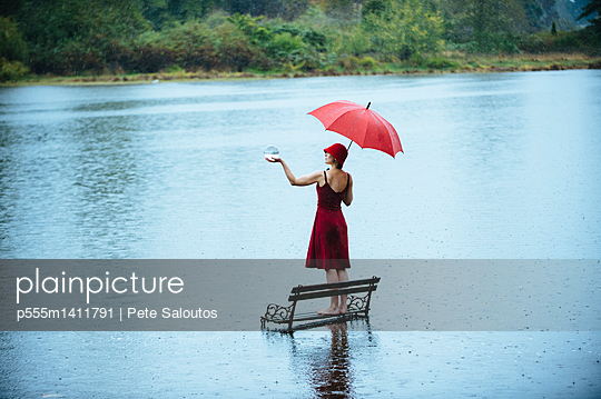 Caucasian woman standing on bench in flood - p555m1411791 by Pete Saloutos