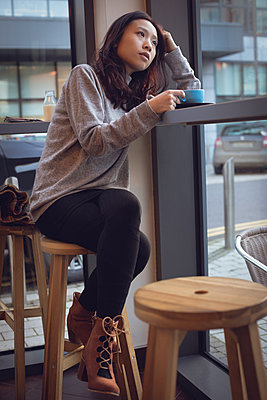 Thoughtful woman having coffee at table in cafeteria - p1315m1566104 by Wavebreak