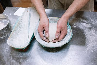 Male baker keeping flour dough in container in kitchen at bakery - p300m2242892 by Jose Luis CARRASCOSA