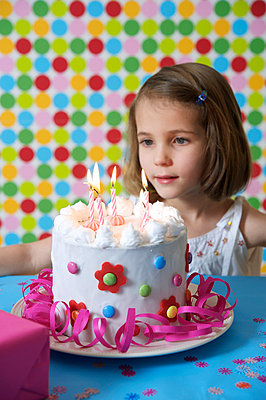 Girl sitting in front of a birthday cake - p5530103 by Christine Basler