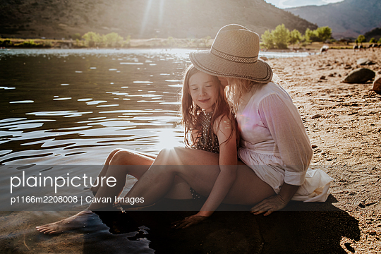 Mom and daughter hugging and having a quiet moment on lakeshore - p1166m2208008 by Cavan Images