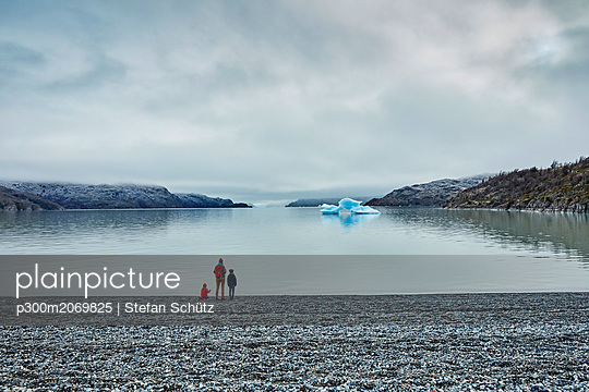 Chile, Torres del Paine National park, Lago Grey, woman with two sons standing at the shore looking at iceberg - p300m2069825 by Stefan Schütz