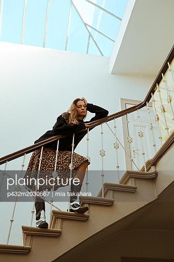 Junge Frau steht Im Treppenhaus - p432m2030667 von mia takahara