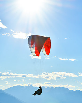 Paraglider flying in blue skies with sunflare - p1166m2162793 by Cavan Images