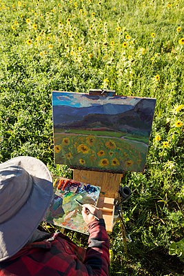 Male painter painting sunflowers in sunny rural field - p1192m1183828 by Hero Images