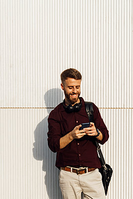 Smiling businessman with headphones and shoulder bag using mobile phone while standing against white wall - p300m2250374 by Boy photography
