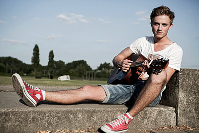 Germany;  Young man playing guitar in park - p300m836914f by Gabi Dilly