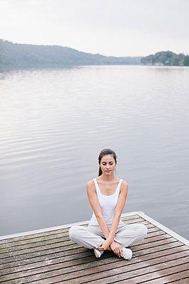 Yoga am See, Frau sitzt mit gekreuzten Beinen - p586m956098 von Kniel Synnatzschke
