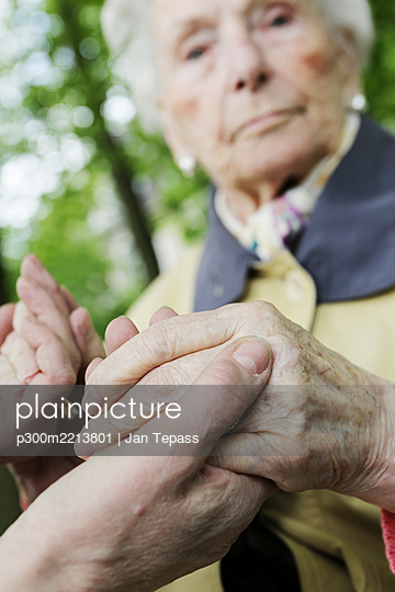 Germany, North Rhine Westphalia, Cologne, Senior woman holding hands of mature woman, close up - p300m2213801 by Jan Tepass