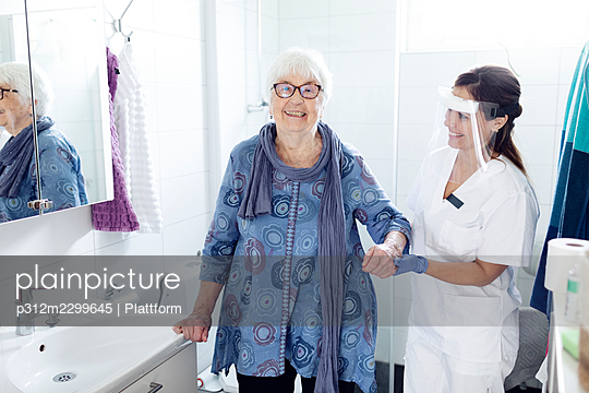 Nurse helping elderly woman in bathroom - p312m2299645 by Plattform