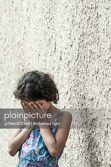 Scared little girl hiding face