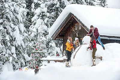 Austria, Altenmarkt-Zauchensee, friends building up big snowman at wooden house - p300m1505512 by Hans Huber