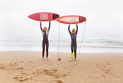 Spain, Aviles, two young surfers on the beach holding their surfboards - p300m2024214 by Marco Govel