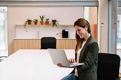 Smiling female entrepreneur with in-ear headphones using laptop while leaning on table at office - p300m2276760 by Xavier Lorenzo