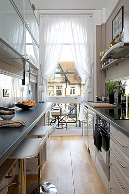 Narrow galley kitchen with white net curtains  Hove  East Sussex  UK - p3493414 by Robert Sanderson