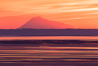 Colorful sunset along Turnagain Arm at low tide with Mt. Redoubt in the background, Southcentral Alaska, spring - p442m1179929 by Doug Lindstrand