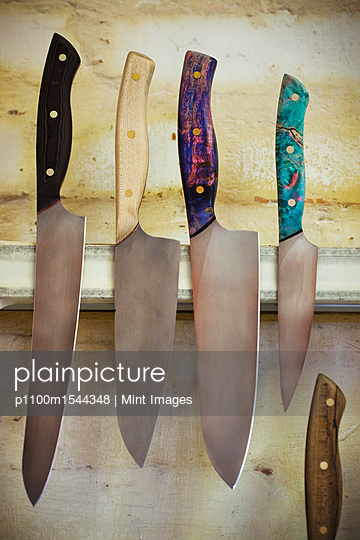 A selection of knives with shaped and painted wooden handles on a magnetic knife holder on a workshop wall.  - p1100m1544348 by Mint Images