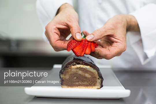 Chef decorating cake with strawberries - p1166m2130360 by Cavan Images
