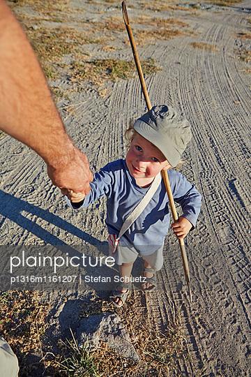Junge geht an der Hand vom Vater in der Steppe, Kubu Island, Makgadikgadi Pans Nationalpark, Botswana - p1316m1161207 von Stefan Schuetz