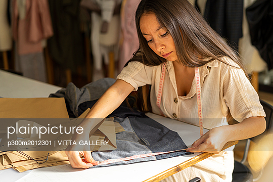 Young fashion designer working in her studio - p300m2012301 von VITTA GALLERY
