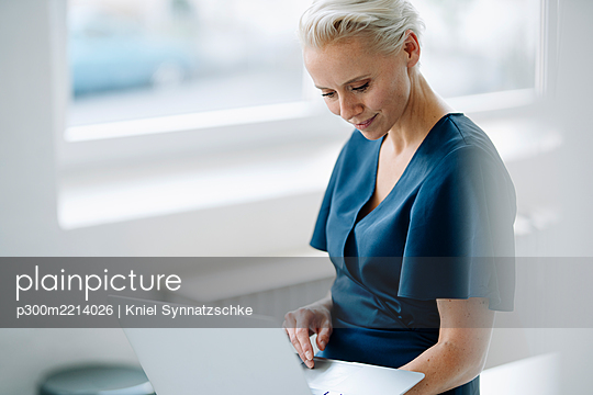 Businesswoman using laptop while sitting in loft office - p300m2214026 by Kniel Synnatzschke