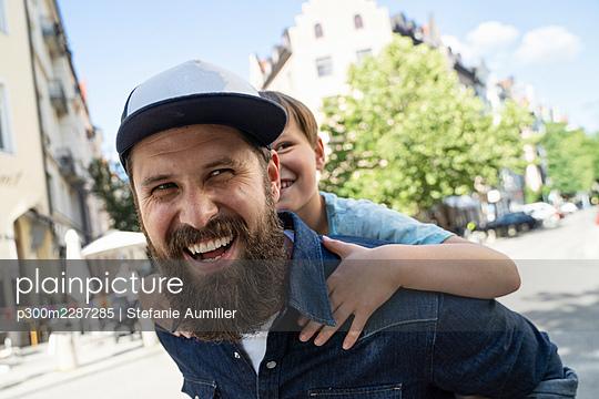 Cheerful man wearing cap piggybacking son on street - p300m2287285 by Stefanie Aumiller