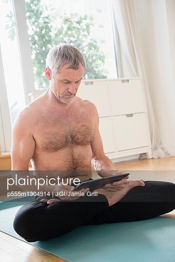 Older Caucasian man using digital tablet on exercise mat