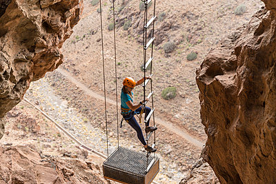 High angle view of female hiker climbing on rope ladder amidst mountains - p1166m1568940 by Cavan Images