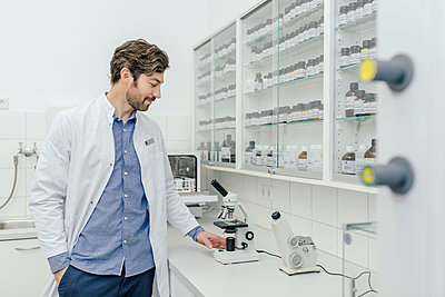 Smiling man with microscope in laboratory - p300m1549670 by Mareen Fischinger