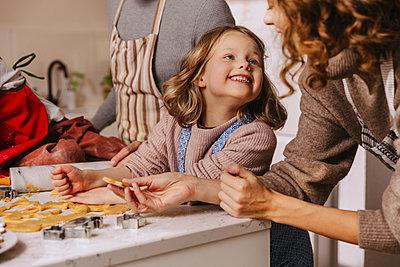 Happy family preparing Christmas cookies in kitchen - p300m2156526 von Mareen Fischinger