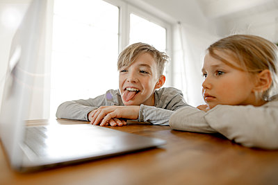 Happy brother and sister looking at laptop together at home - p300m2180301 by Katharina Mikhrin