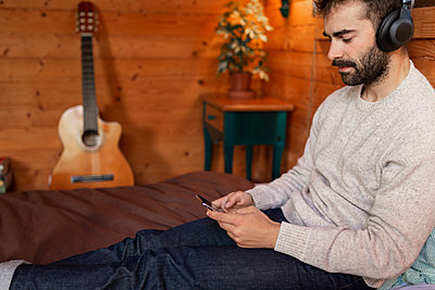 Young man listening music while using mobile phone in wooden house - p300m2243015 by Sus Pons