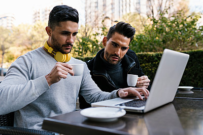 Male friends looking at laptop while having coffee sitting at sidewalk cafe at street - p300m2251734 by Ezequiel Giménez