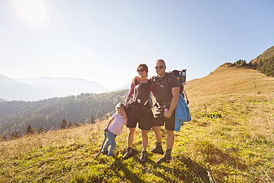 Family hiking together on hillside - p42918426f by Matelly