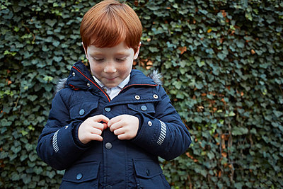 Portrait of red haired boy in front of ivy wall fidgeting with hands - p429m1417772 by Emma Kim