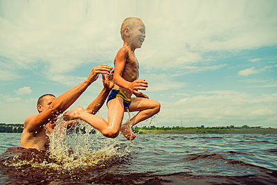 Caucasian father and son swimming in lake - p555m1411599 by Aleksander Rubtsov