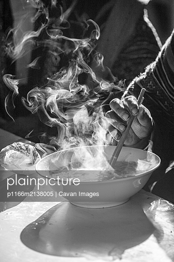 Hmong woman taking a steaming pho bowl (vietnamese soup) - p1166m2138005 by Cavan Images
