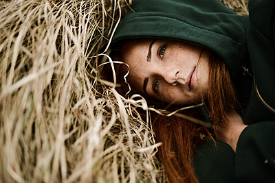 Close-up portrait of teenage girl with red head lying on grassy - p1166m2113132 by Cavan Images