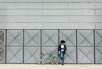 Businessman with bicycle leaning against a wall reading book - p300m2104575 von Valentina Barreto