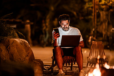 Smiling man with phone using laptop at night - p426m2205331 by Maskot