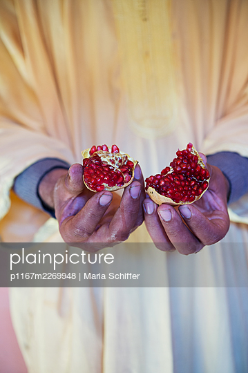 Man holding pomegranate in his hands - p1167m2269948 by Maria Schiffer