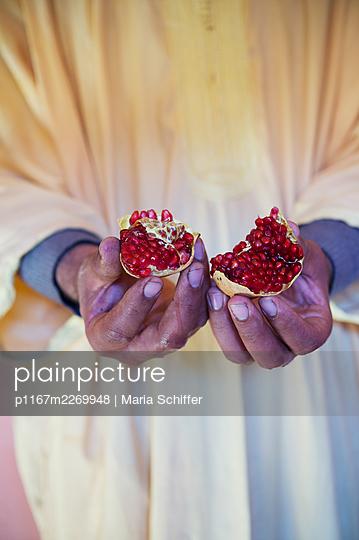 Mann hält Granatapfel in den Händen - p1167m2269948 von Maria Schiffer