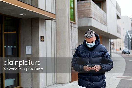Man wearing face mask walking along street - p312m2237121 by Lisa Öberg