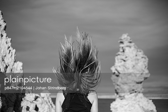 Rear View Of A Woman With Windswept Hair Standing Against Sky   - p847m2104844 by Johan Strindberg